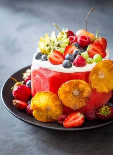 Vegan Watermelon Cake on a black plate decorated with fresh fruit.