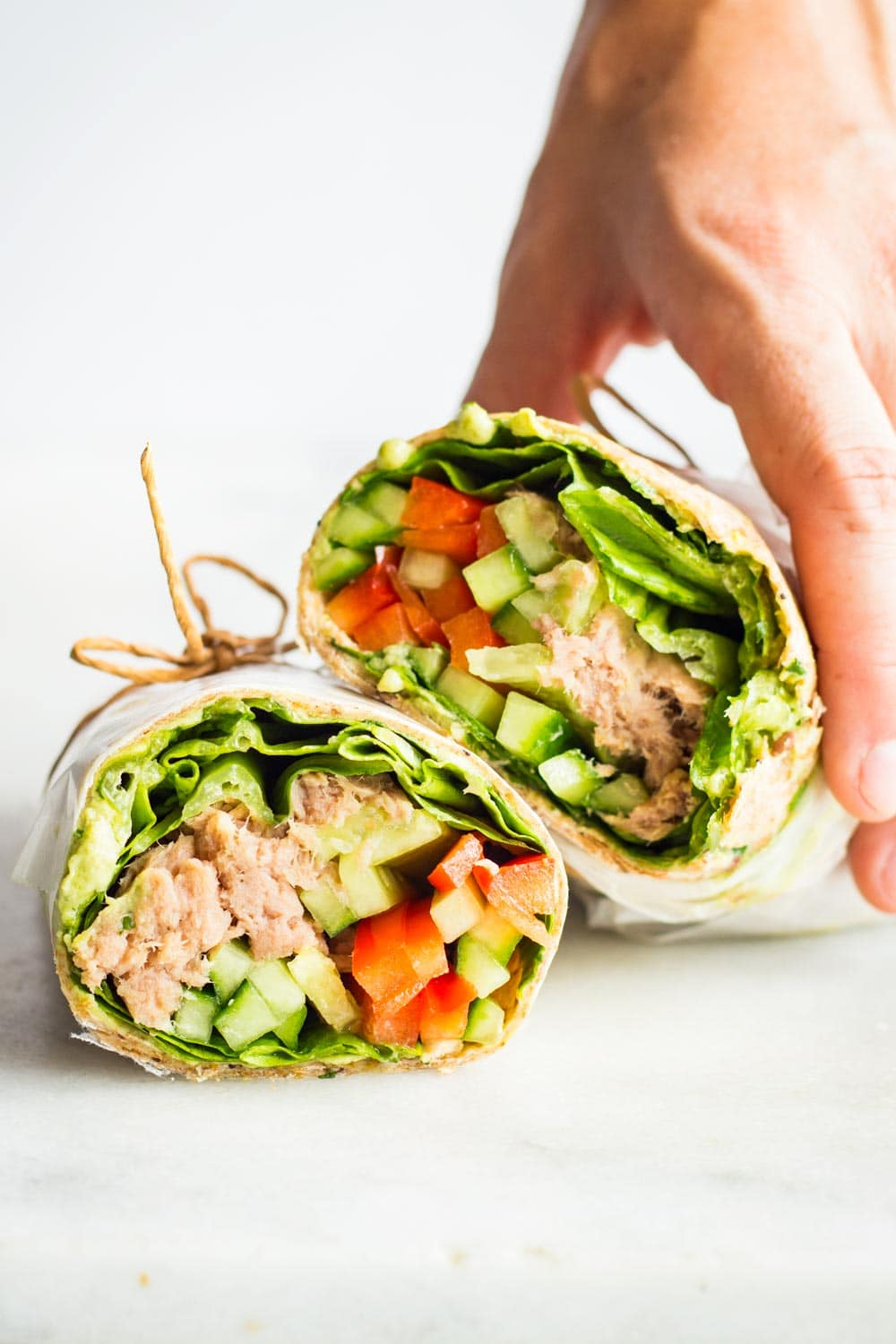 Hand holding a Healthy Tuna Wrap cut in two halves tied with jute twine.