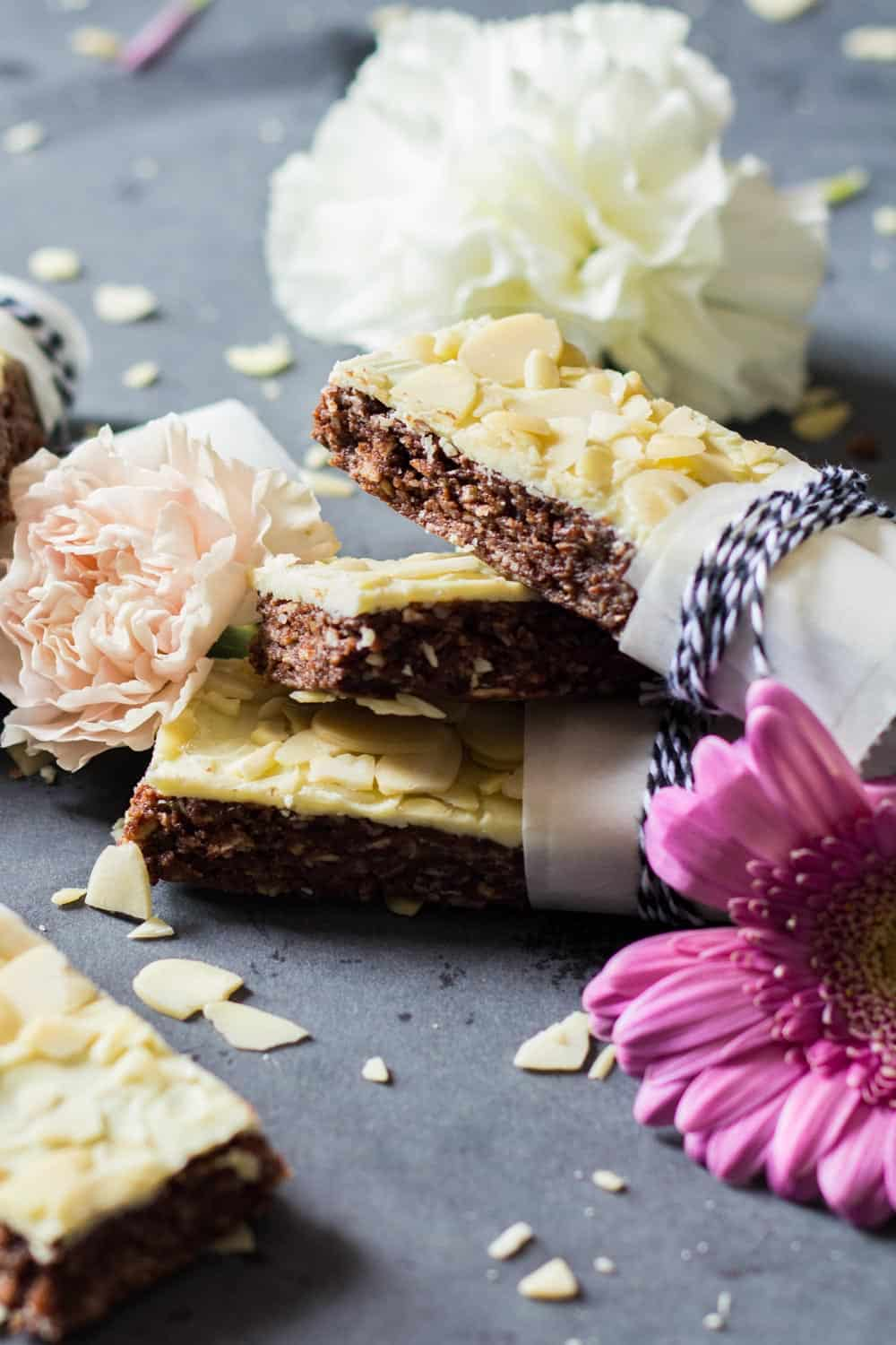 Almond Granola Bars stacked unevenly on a counter decorated with fresh flowers and sliced almonds.