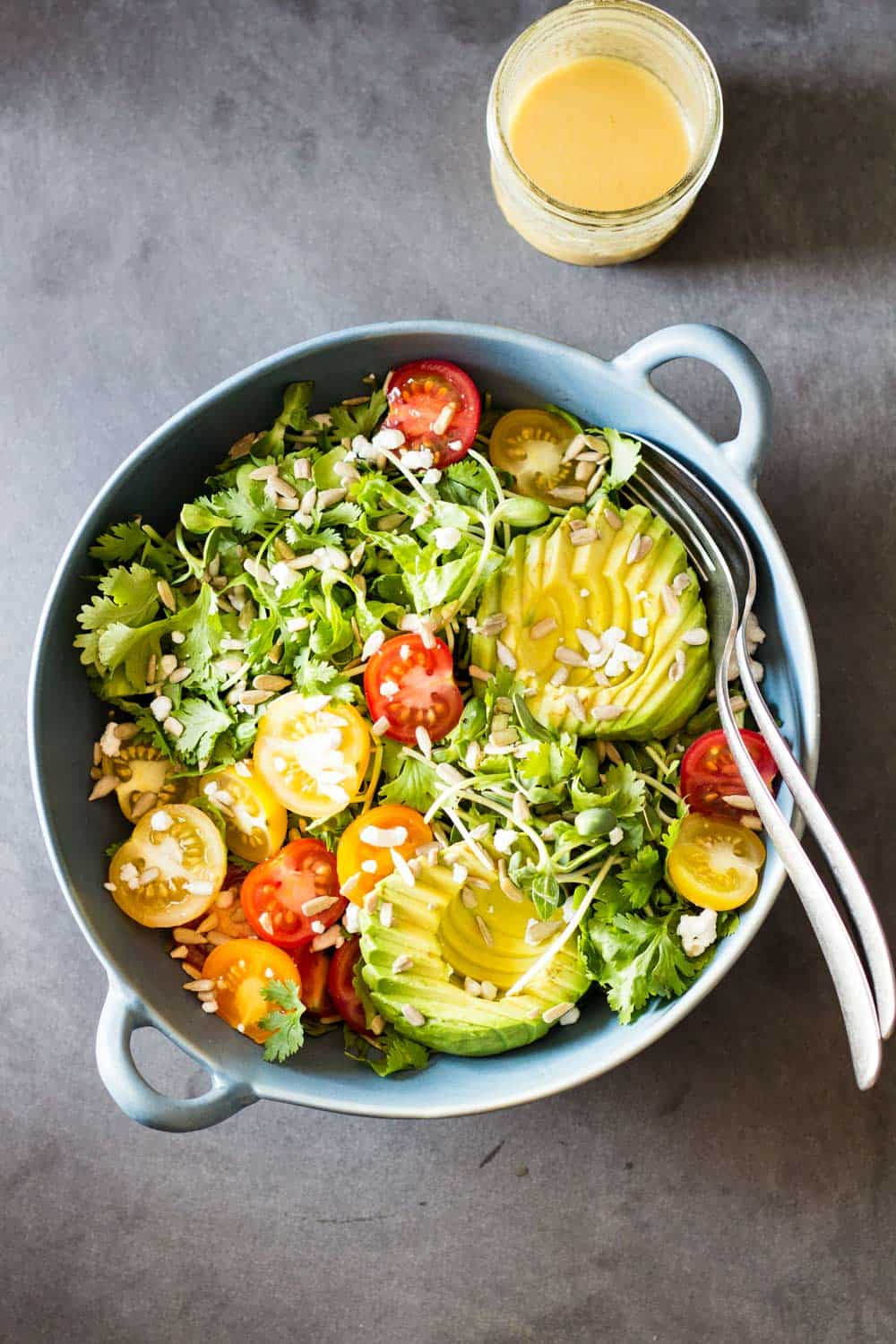 Top view of Mexican-Style Side Salad in a blue ceramic bowl with a fork and a spoon, and a jar of honey lime dressing.