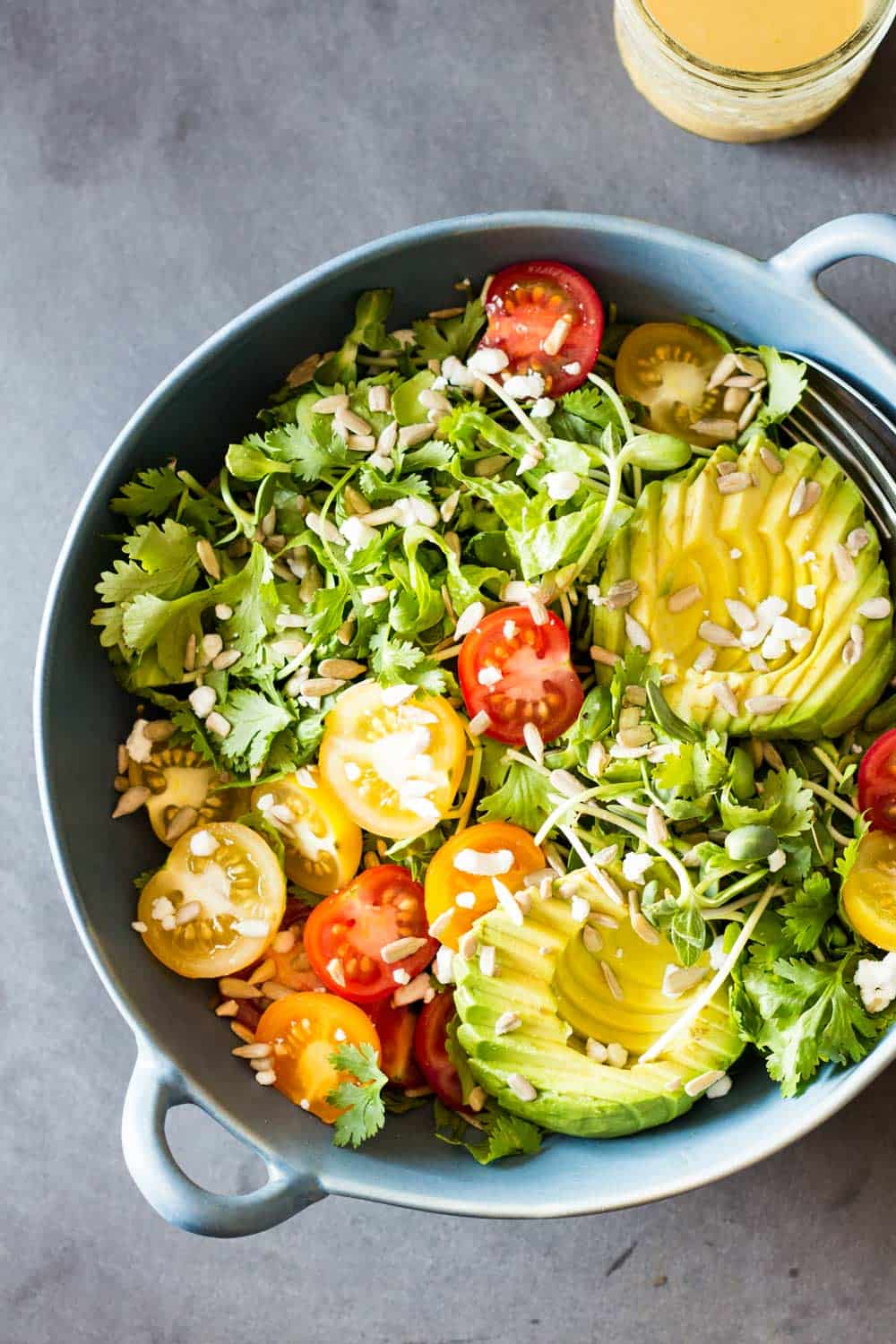 Top view of Mexican-Style Side Salad in a blue ceramic bowl, and a jar of honey lime dressing.
