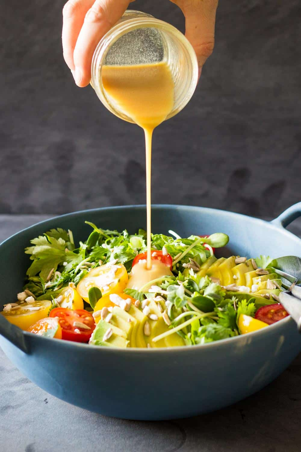 Honey lime dressing being poured over Mexican-Style Side Salad in a blue bowl.