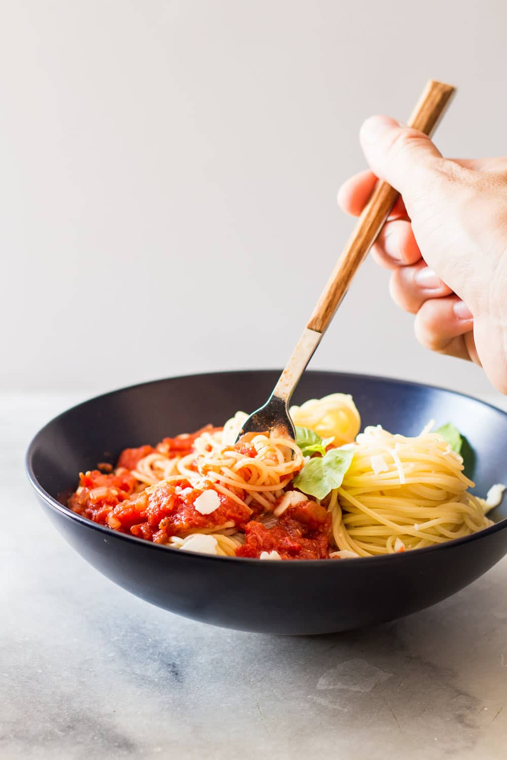 Hand grabbing some Capellini pasta with Roasted Garlic Tomato Sauce with a fork.