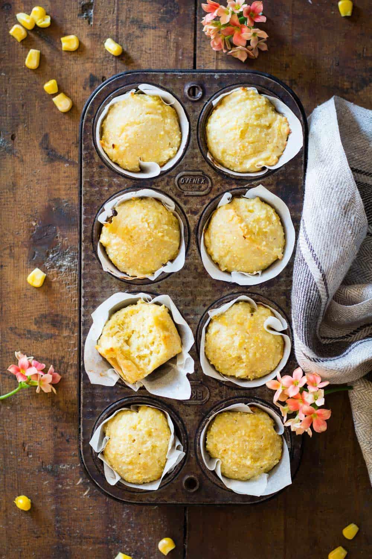 Cornbread muffins in parchment paper in a muffin tin.