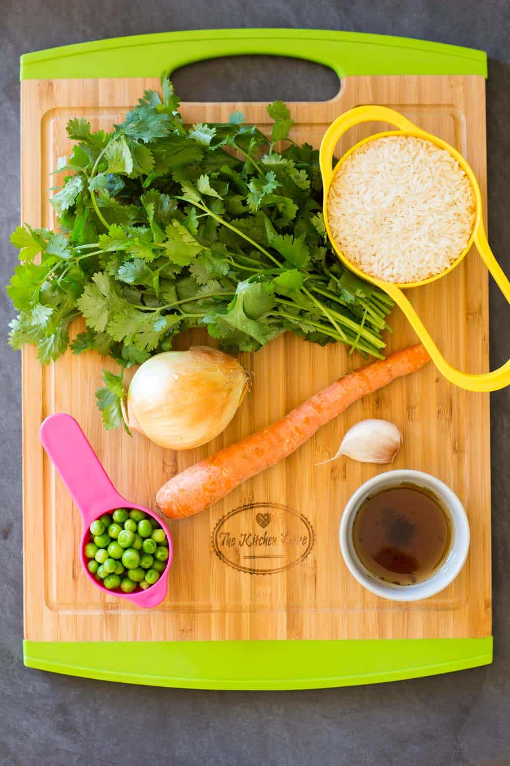 Fresh coriander, rice, broth, garlic, carrot, peas, and onion, on a wooden chopping board.