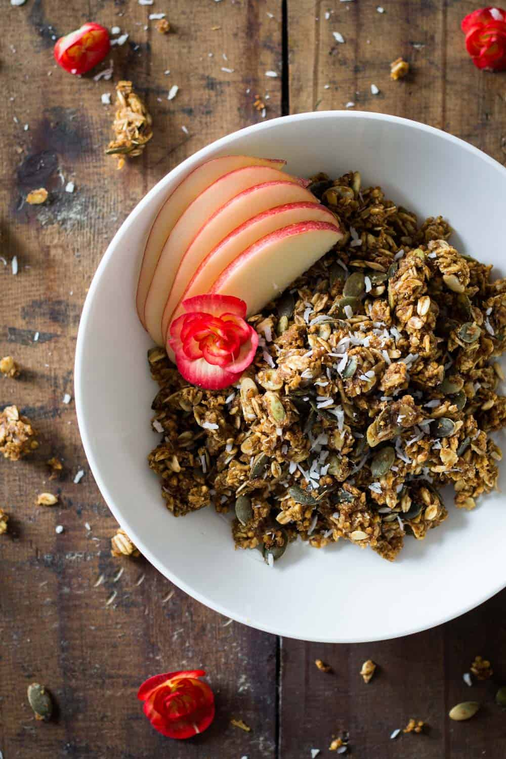 Healthy Pumpkin Granola in a white bowl with sliced apple.