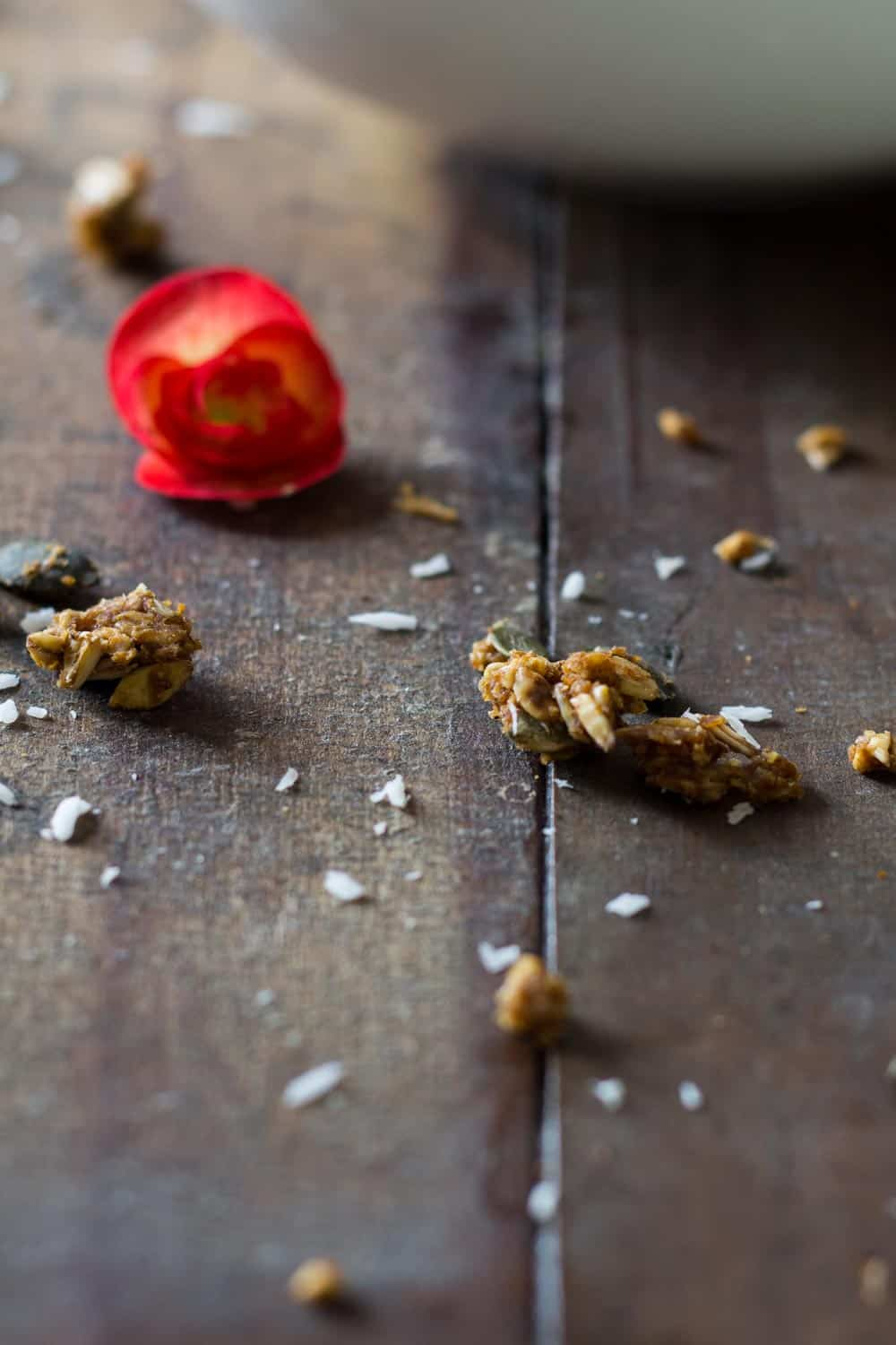Close up of a piece of Healthy Pumpkin Granola on a rustic wooden table an a fresh flower.