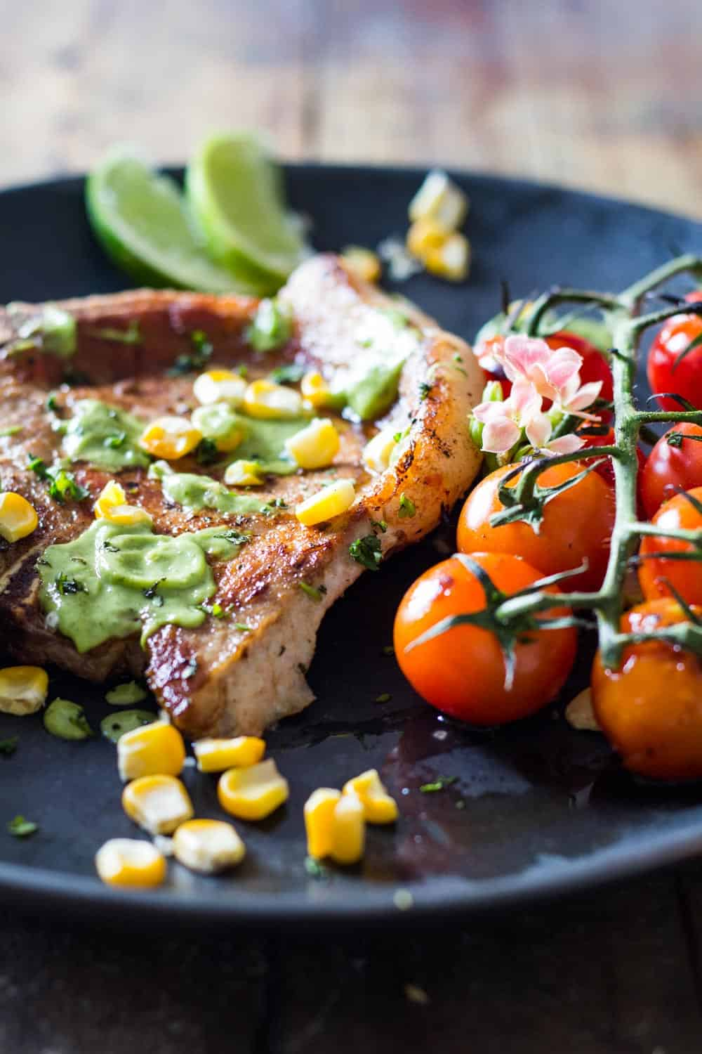 Close up of Pork Chops garnished with avocado cilantro sauce, corn kernels, and cherry tomatoes, to show texture.