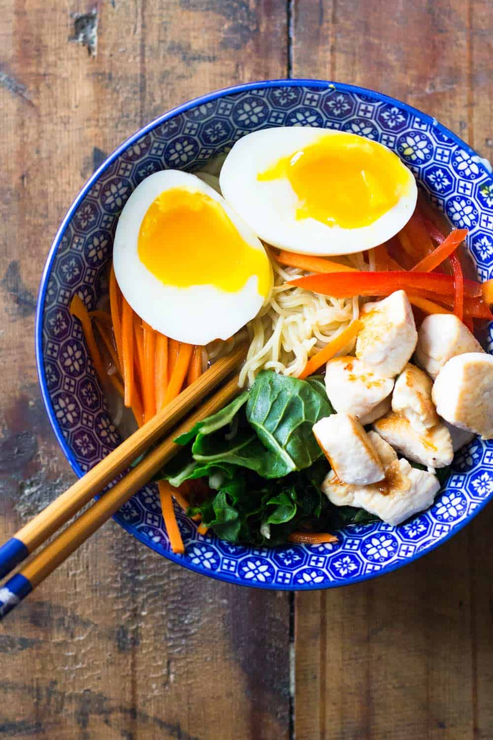 Ramen chicken noodle soup with boiled egg cut in half, served in a blue bowl with chopsticks.