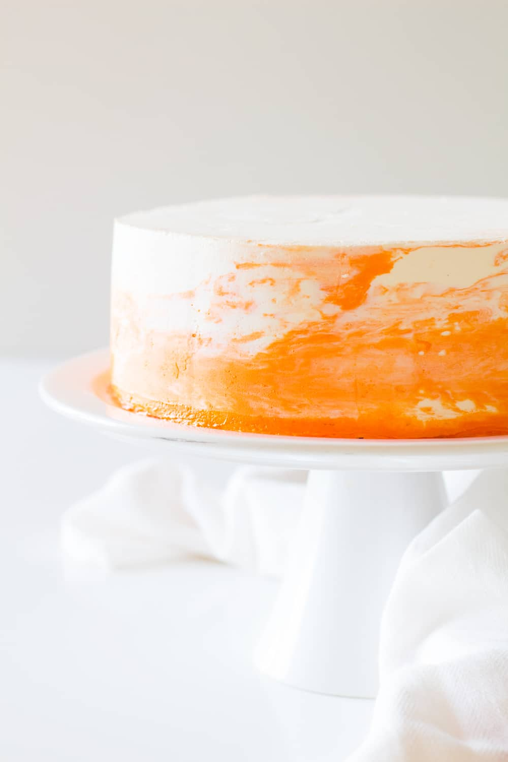 Vanilla cake with white and orange coconut cream frosting on a white cake stand.