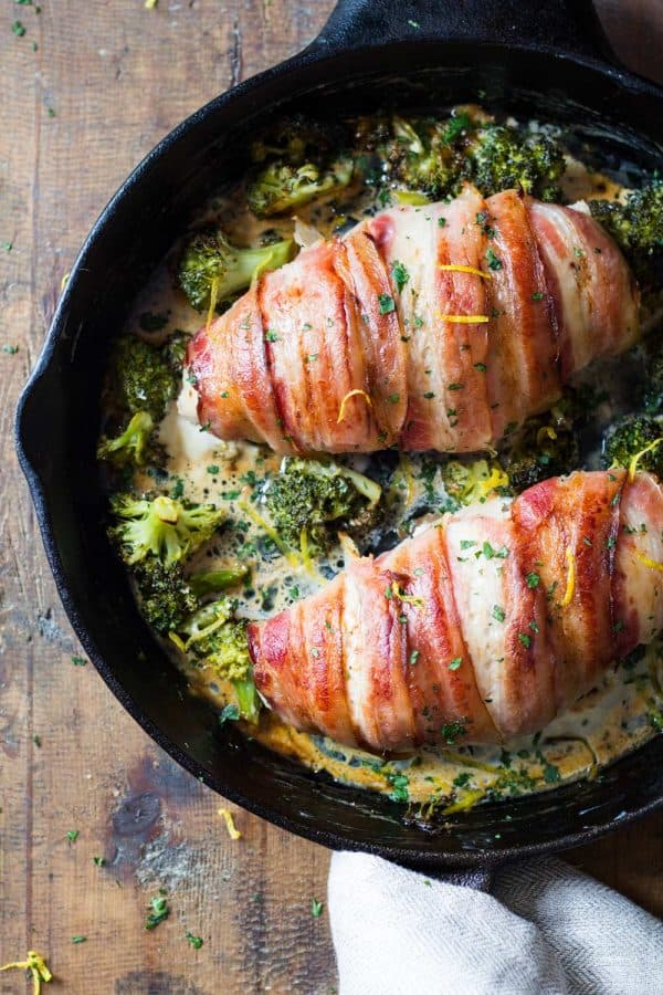 Bacon wrapped chicken breast in a pan with brocooli and creamy suace