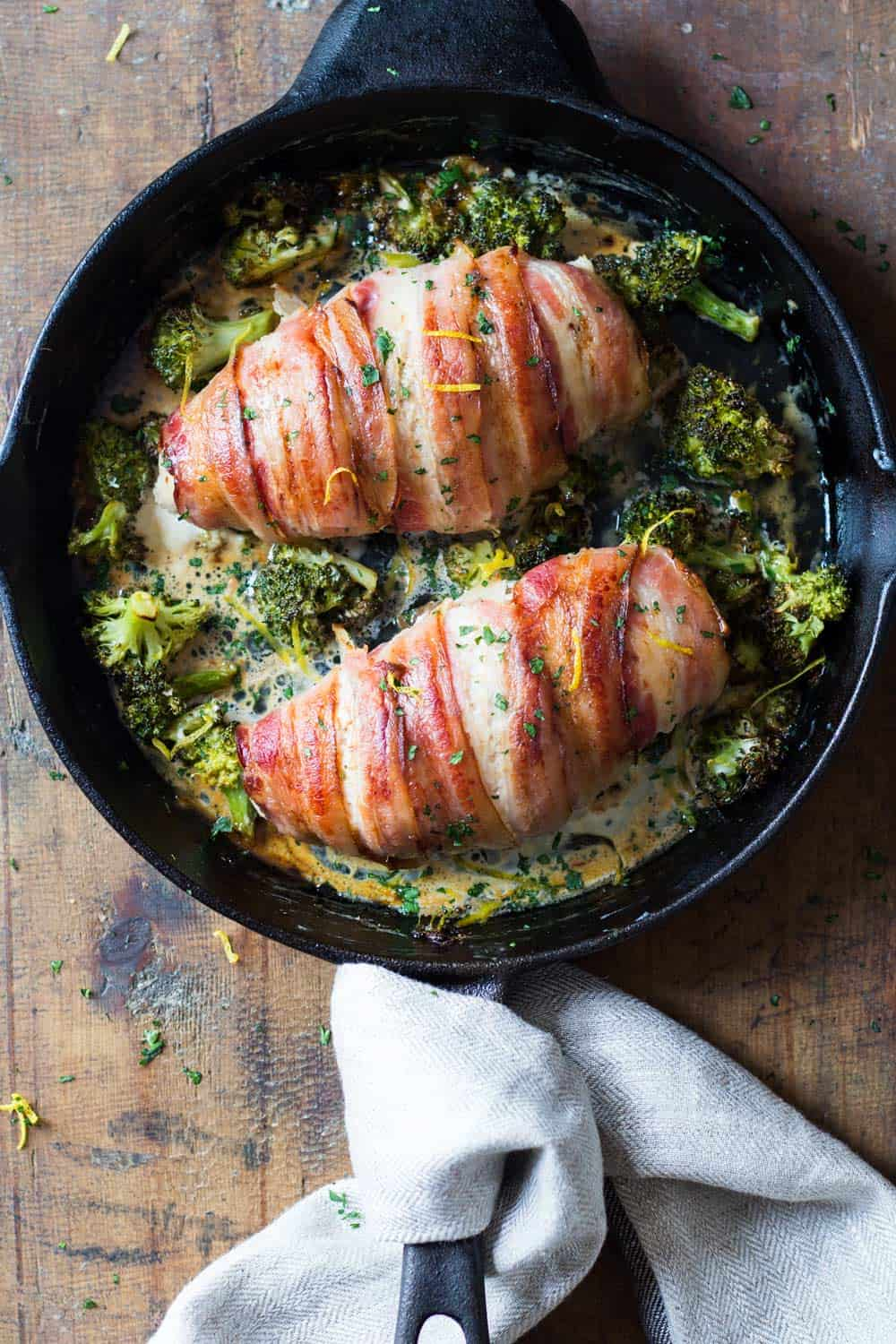Top down view of baked bacon-wrapped chicken breast in black pan with broccoli
