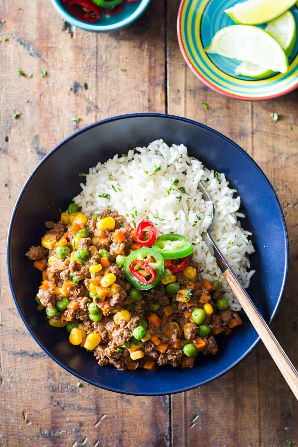 Mexican Picadillo in a blue bowl on a wooden table.