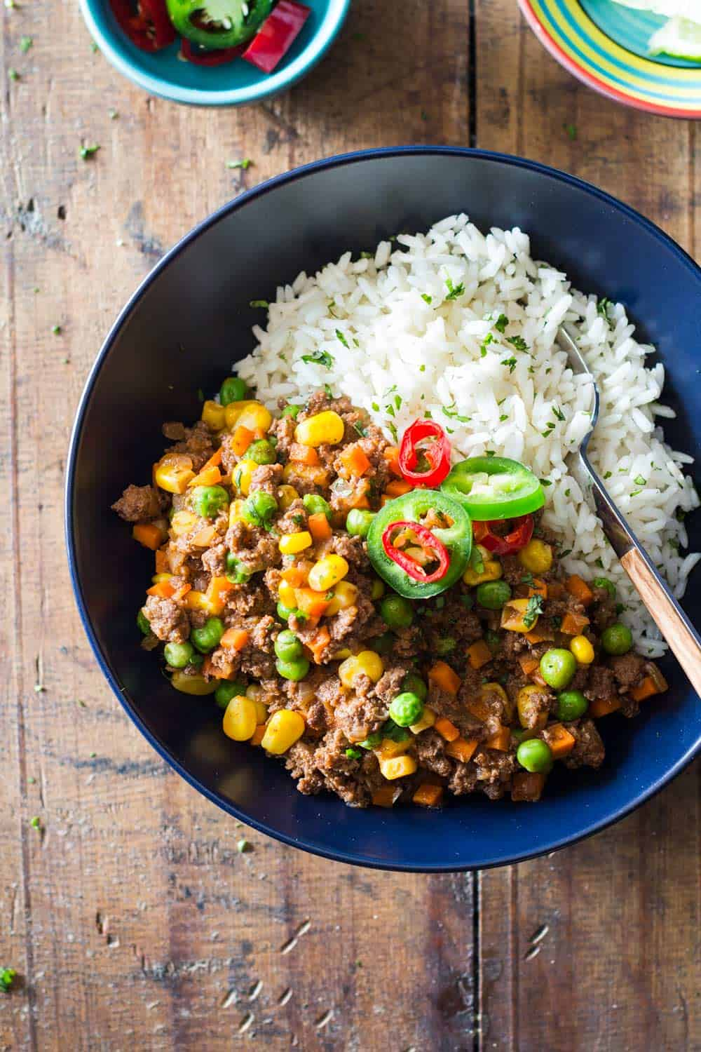 top-down view of picadillo, mexican recipe, served over white rice in a blue bowl.