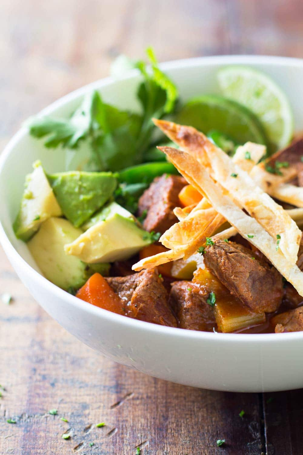 Snowy and cold winter days scream for hearty Mexican Beef Stew topped with delicious avocado, spicy jalapeño, crispy tortilla and juicy lime wedges!