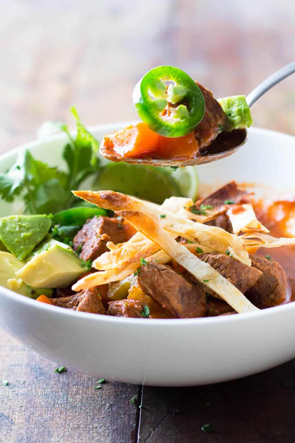 Mexican beef stew served in a white bowl and a spoonful of stew showing ingredients.