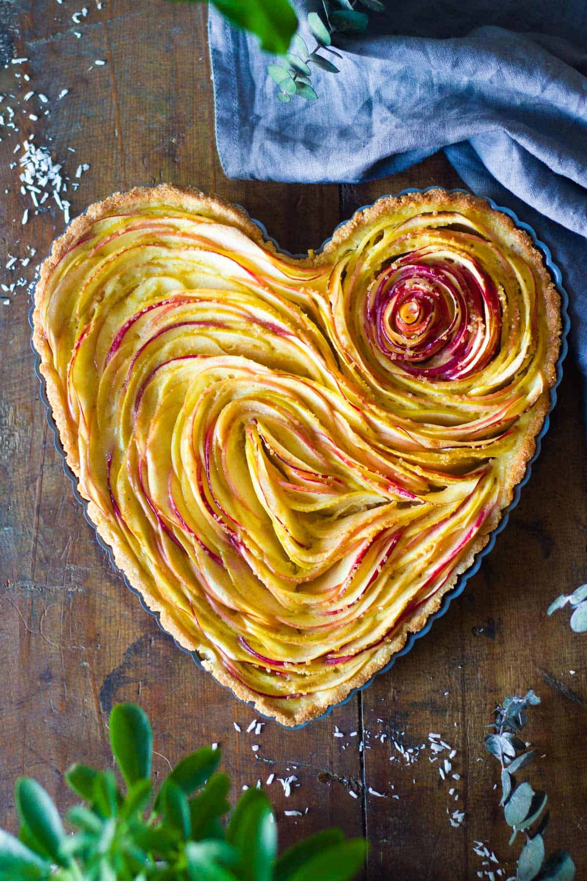 Baked apple tart in heart-shaped tart pan.