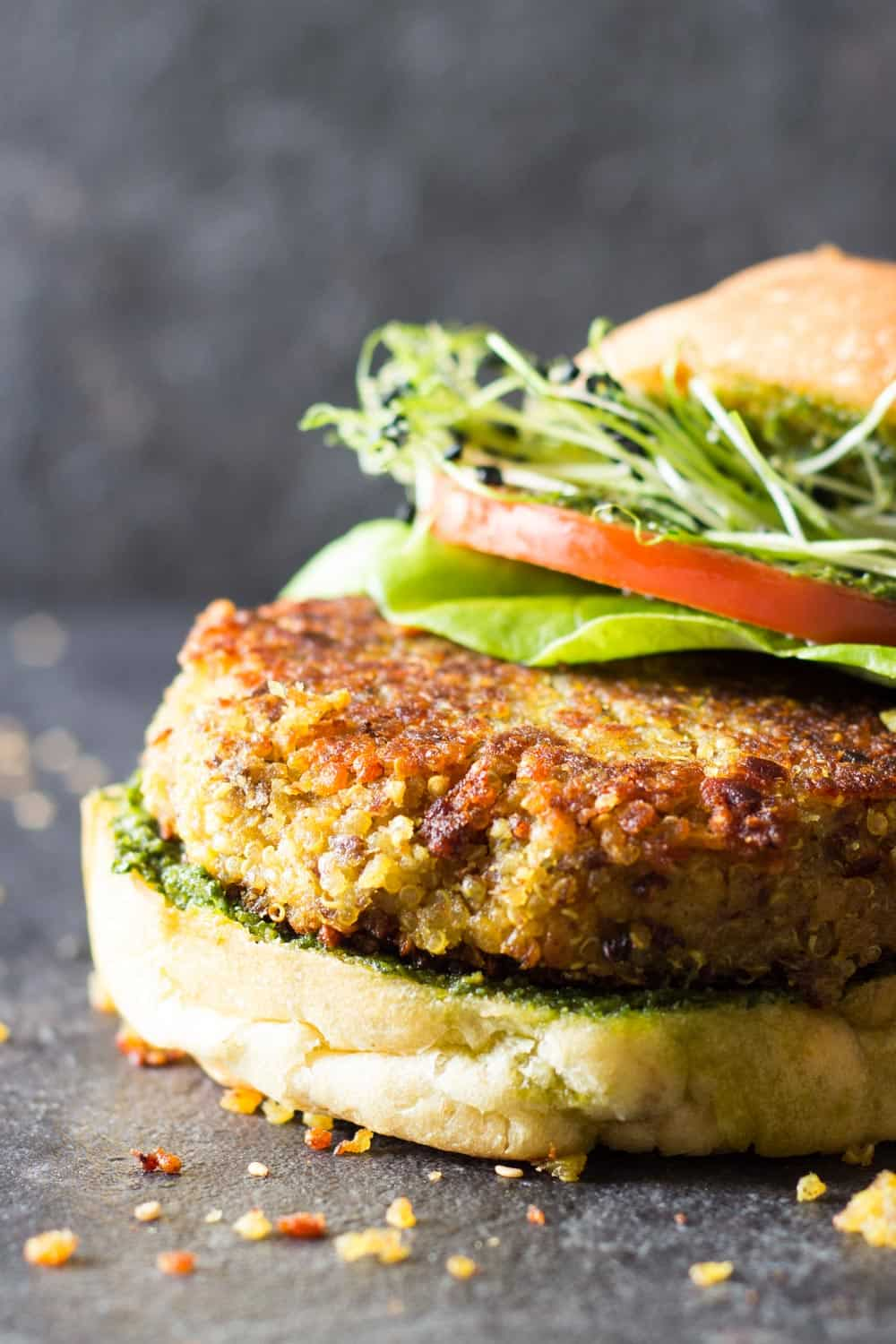 Detail of quinoa veggie burger to show texture, in a bun with lettuce, tomato, micro greens and basil pesto sauce.