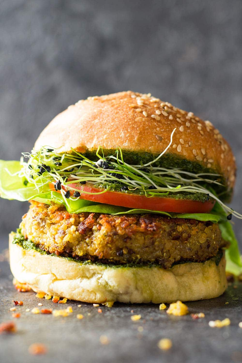 Side view of quinoa burger in a bun with lettuce, tomato, micro greens and basil pesto sauce.