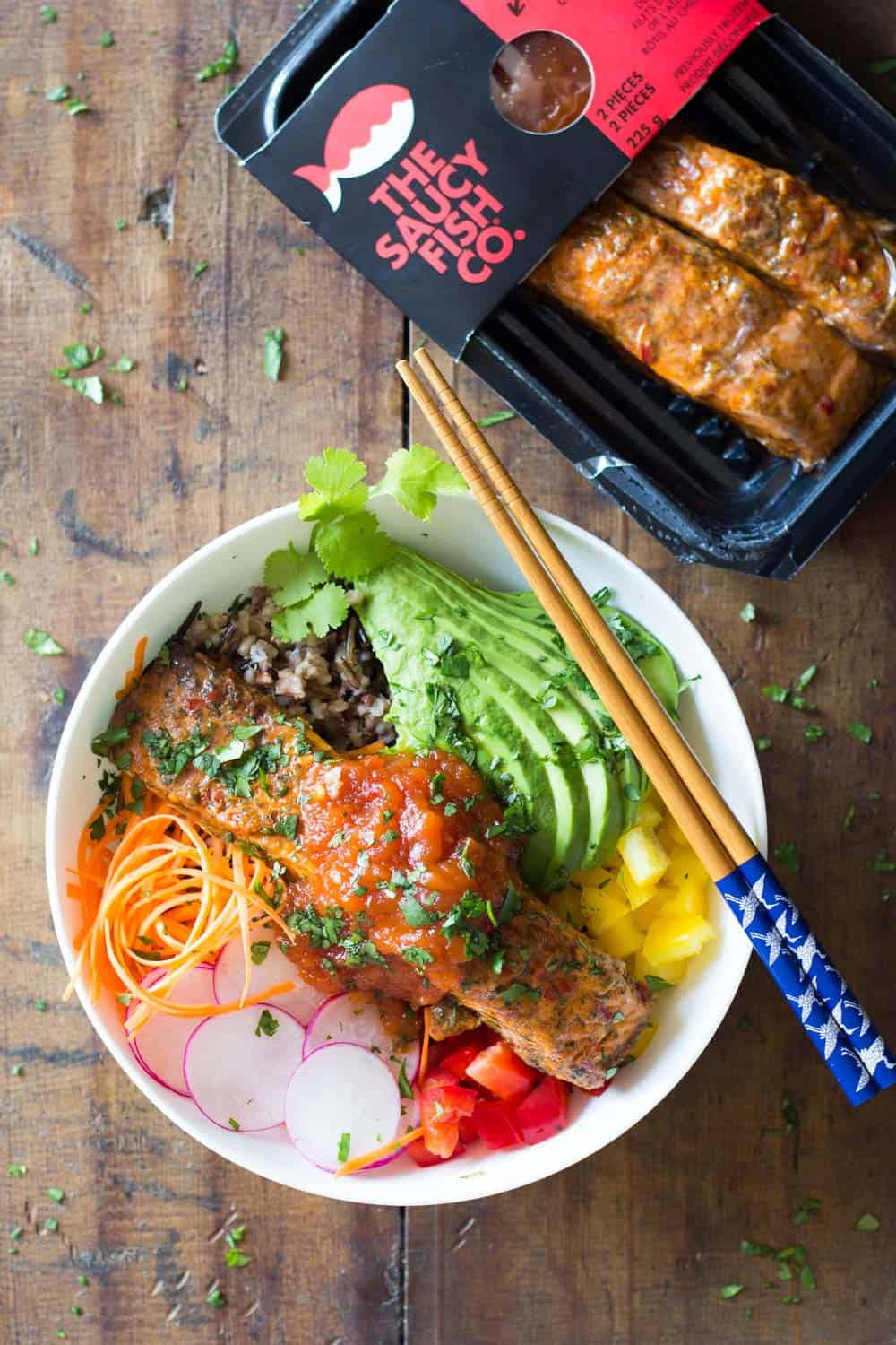 Package of cooked salmon by The Saucy Fish Co. and a bowl of salmon poke salad with avocado, yellow and red pepper, radish, veggie noodles and wild rice, topped with sauce.