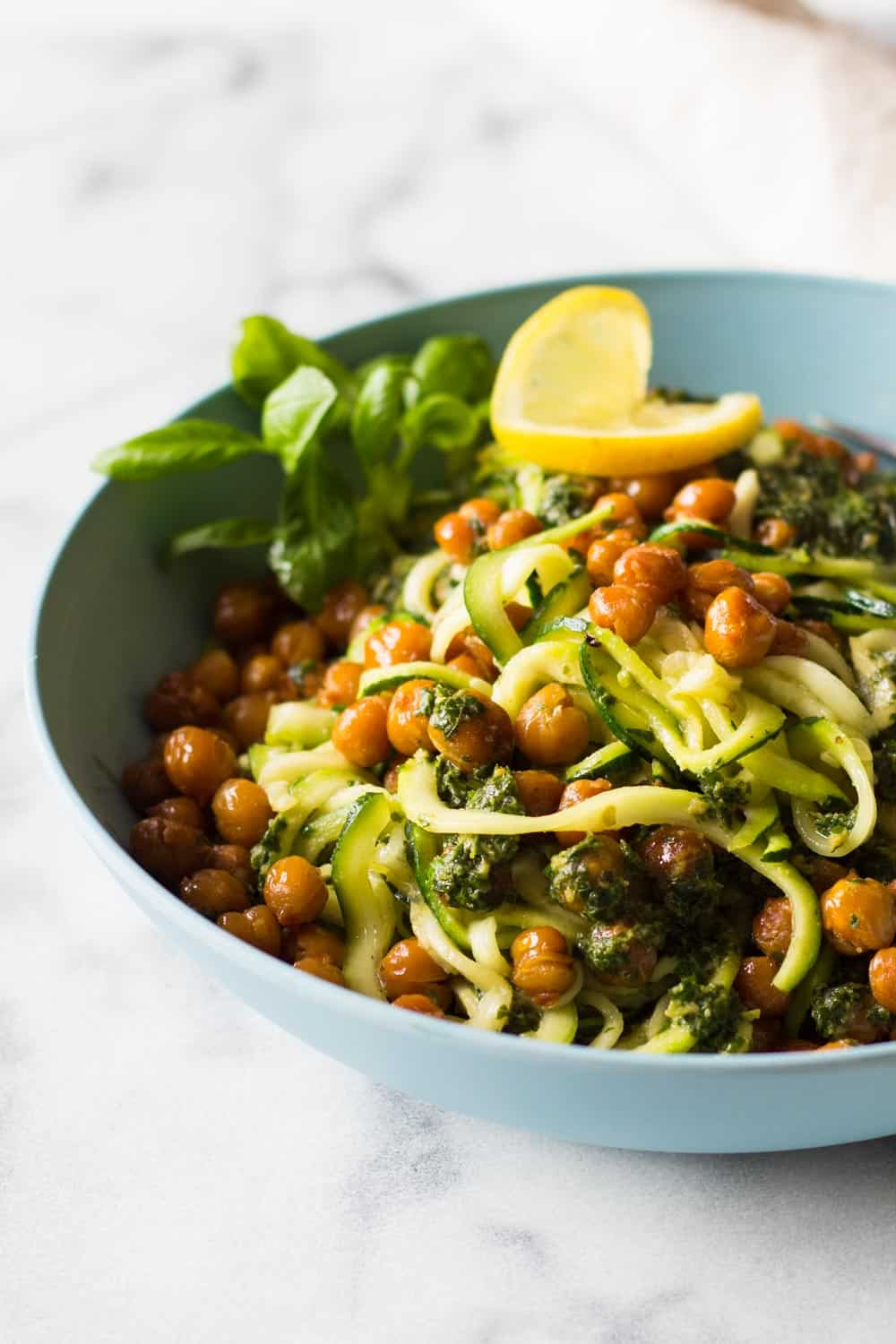 Zucchini noodles with roasted chickpeas and herb sauce, garnished with lemon slice and basil leaves, in a blue bowl.