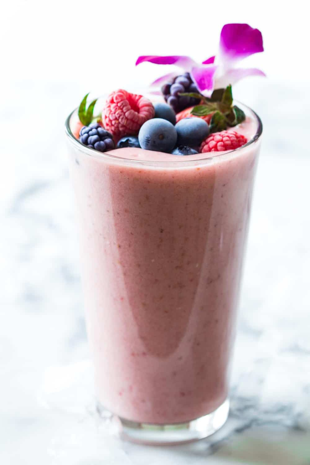 Glass of strawberry banana smoothie without yogurt filled to the rim, topped with raspberries, blueberries, blackberries and strawberries.