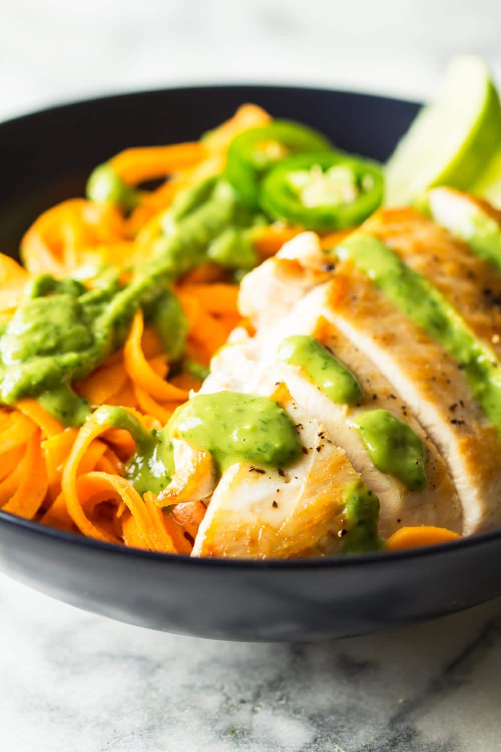Texture of sliced chicken breast with sweet potato noodles on the side, topped with cilantro and avocado dressing.