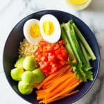 Instant Pot Quinoa Bowl with hard-boiled egg, cucumber, carrots, tomatoes, avocado and lemon tahini dressing.