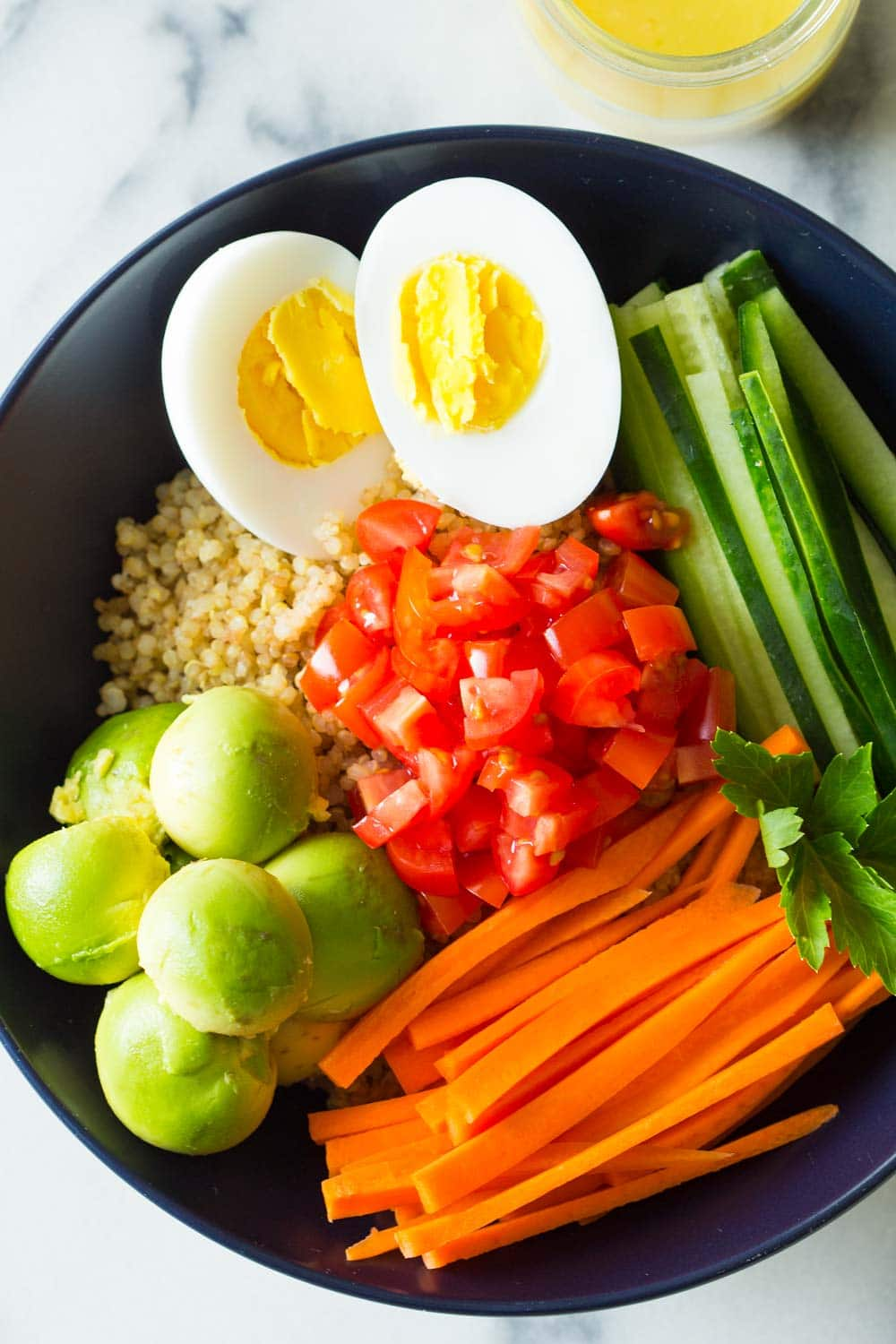 Instant Pot Quinoa Bowl with hard-boiled egg, avocado, carrot, cucumber and tomato