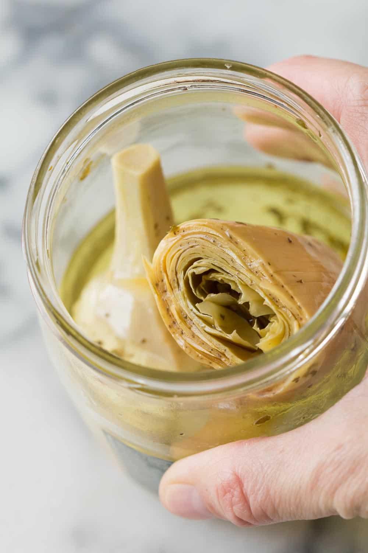 Close up of a hand holding an open artichoke hearts jar.