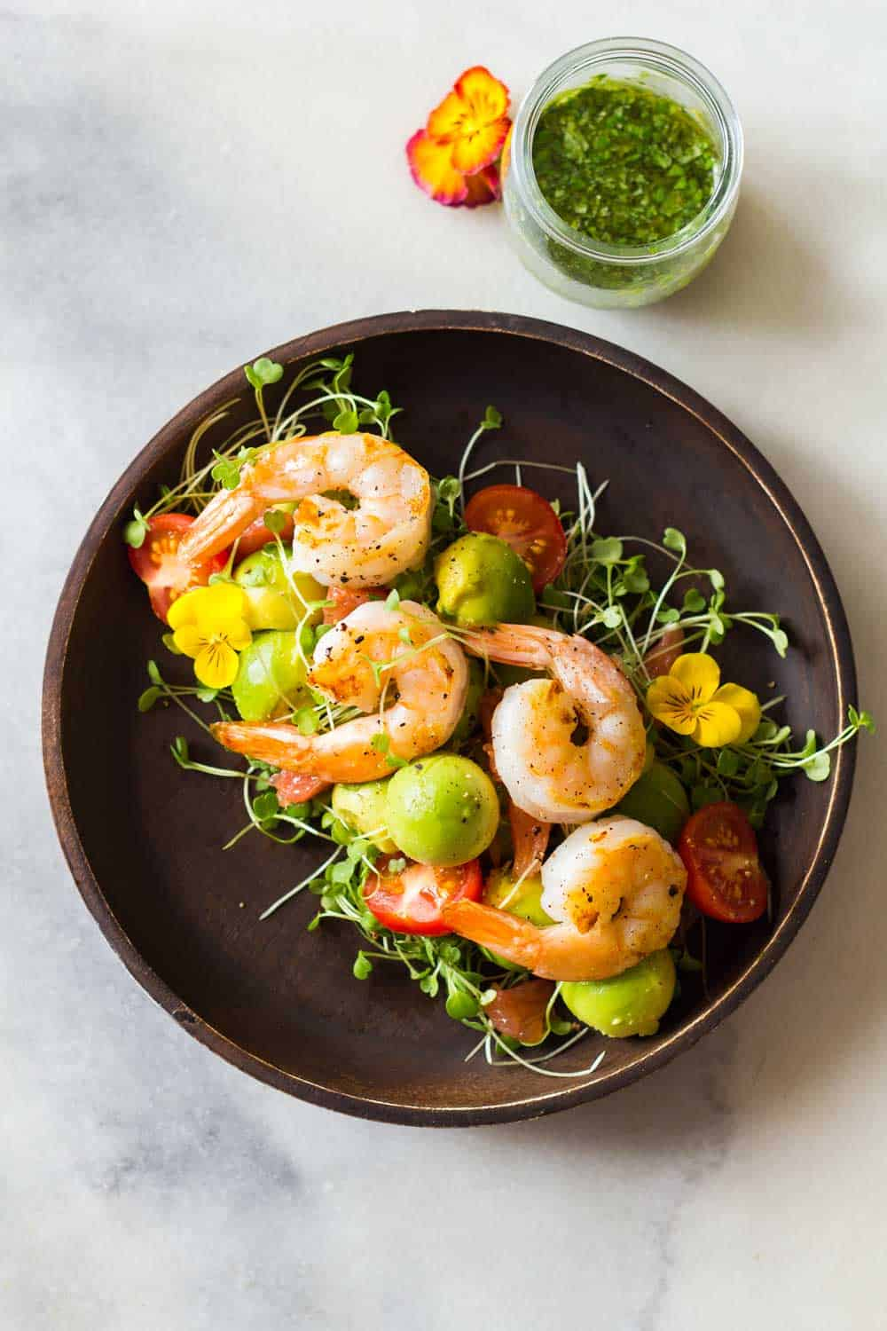 Shrimp, avocado, tomato, arugula and grapefruit on a plate with cilantro dressing in a jar.