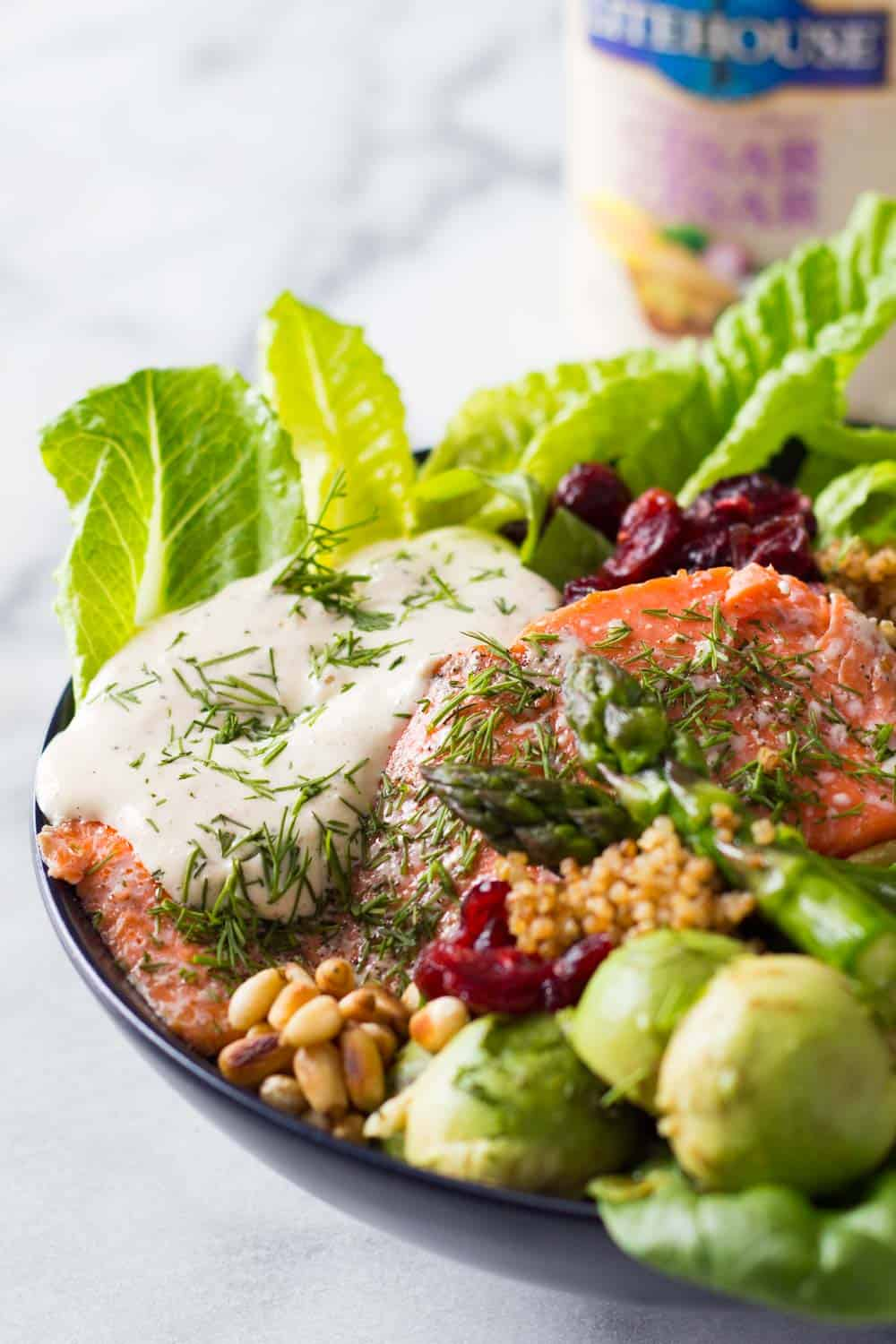 Baked Sockeye Salmon topped with creamy caesar dressing and served with lettuce leaves, dried cranberries, pine nuts, asparagus, avocado balls and quinoa.