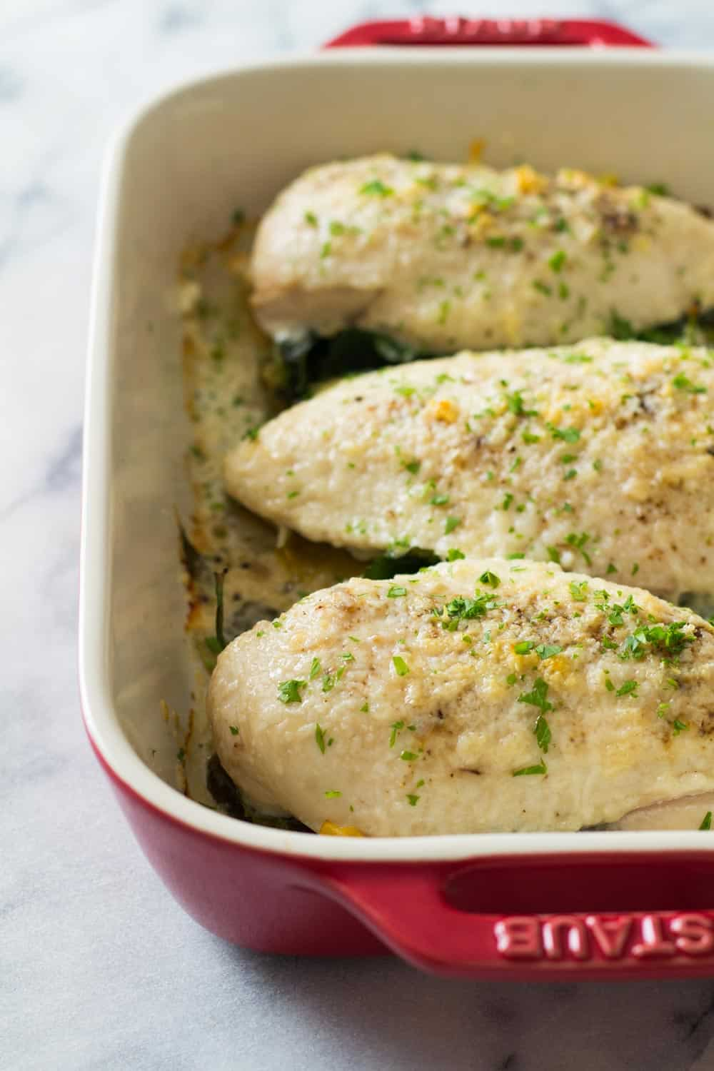 Baked spinach artichoke chiken breasts in a red baking dish.