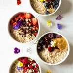 Four Instant Pot Steel Cut Oats bowls with different toppings, garnished with fresh flowers.