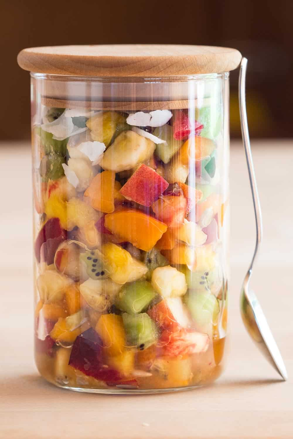 Mango Fruit Salad in a jar with a spoon leaning against it.