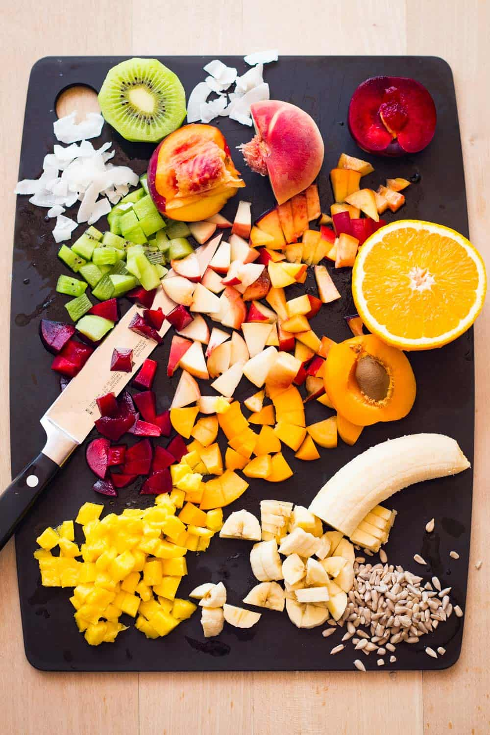 Ingredients for a mango fruit salad - mango, banana, stone fruit, kiwi, seeds, dried coconut