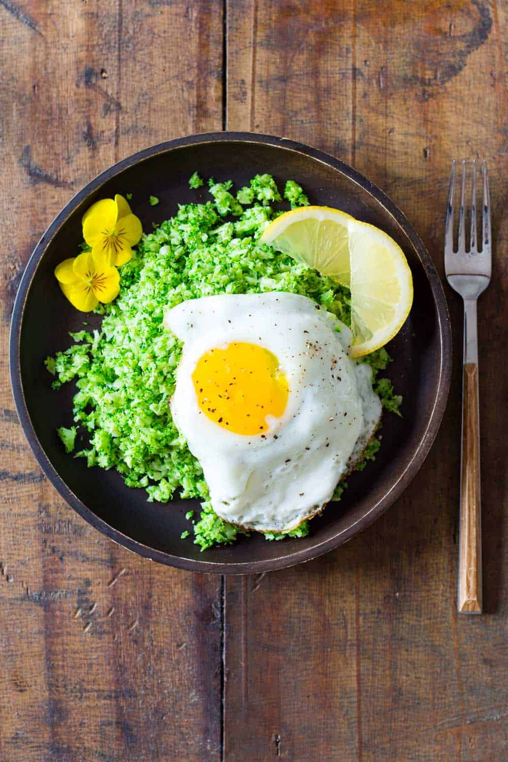 Broccoli rice served on a wooden plate, topped with a fried egg and lemon slices