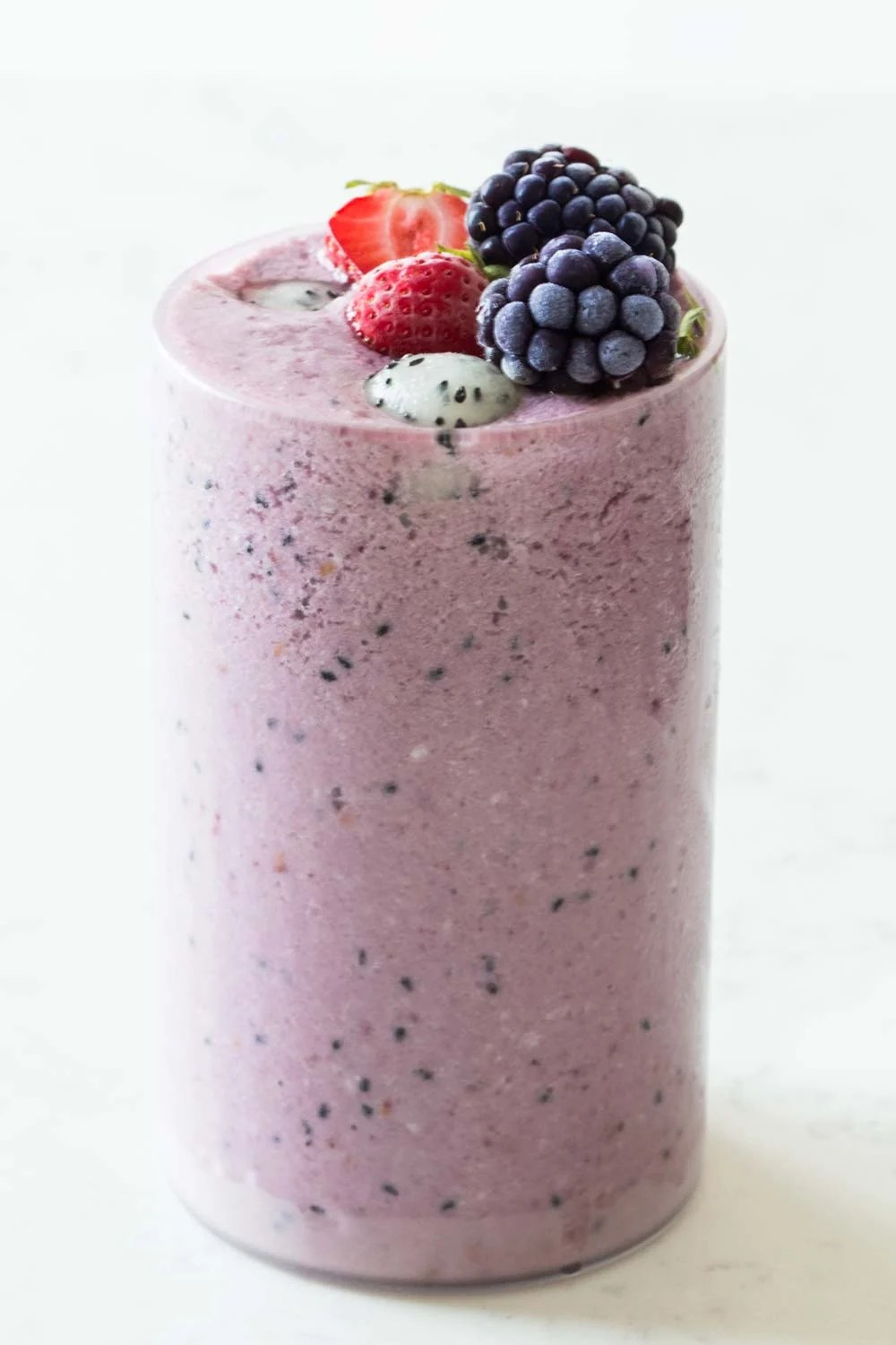 Tall glass filled to the rim with dragon fruit smoothie topped with strawberries, blackberries and balls of dragon fruit