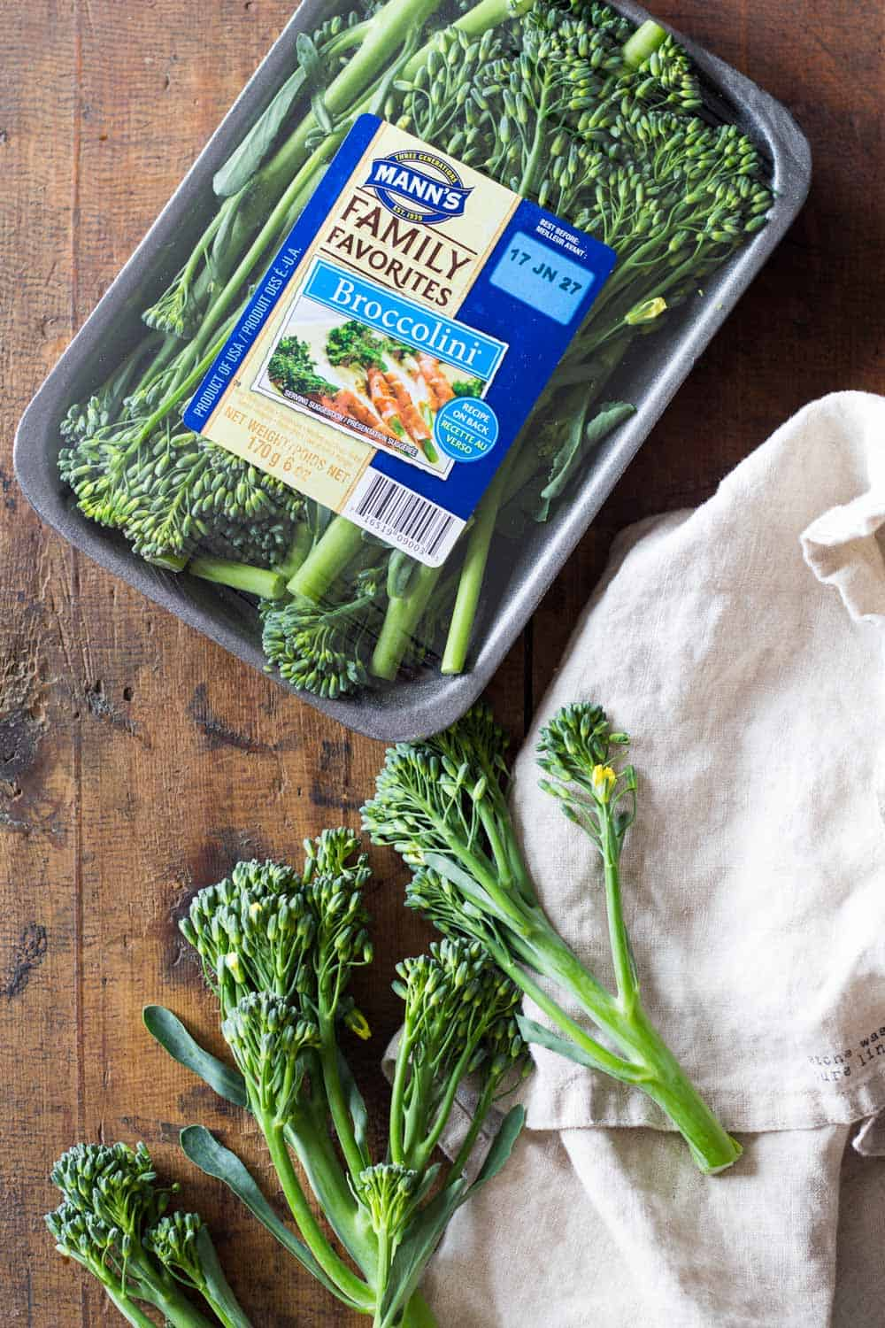 Mann's broccolini package and loose broccolini branches presented outside the package on a table