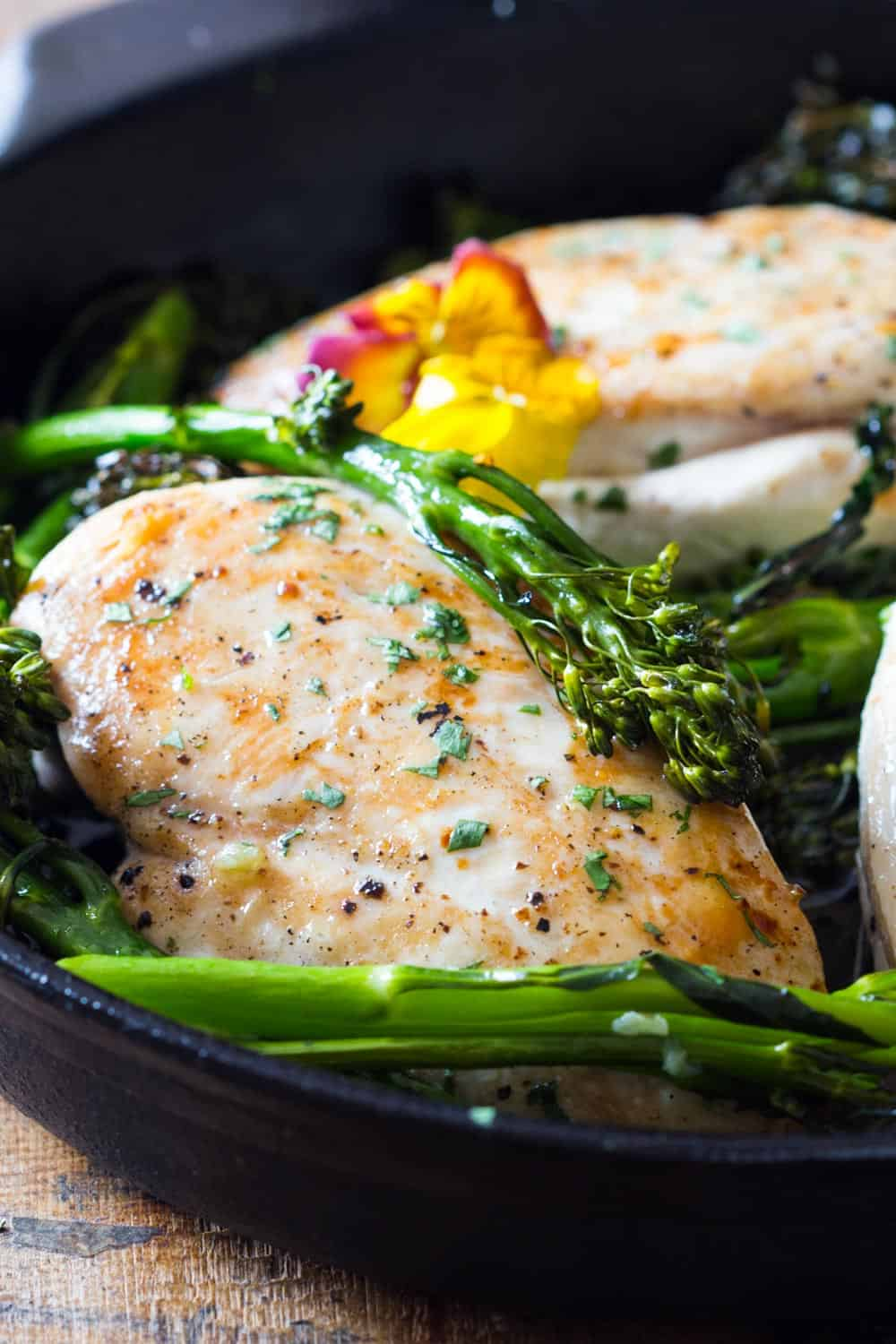 Cooked chicken breast with broccolini on a plate