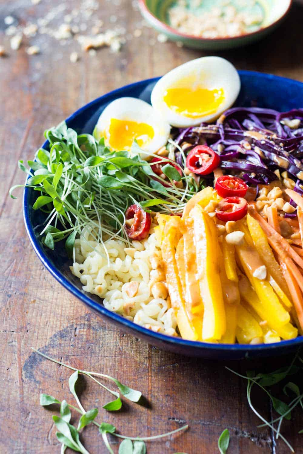 Ramen noodle salad with veggies and soft-boiled egg topped with peanut sauce, presented in a blue plate