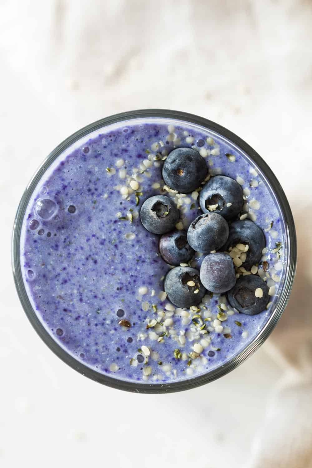 top down view of blue smoothie with blueberries