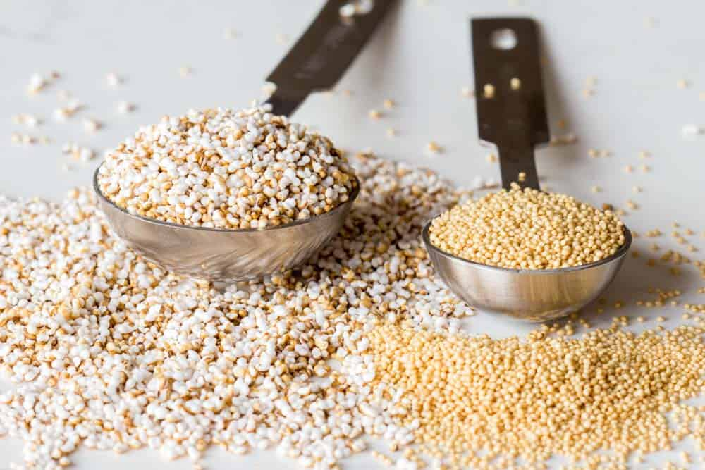A measuring spoon with popped amaranth and a measuring spoon with raw amaranth.