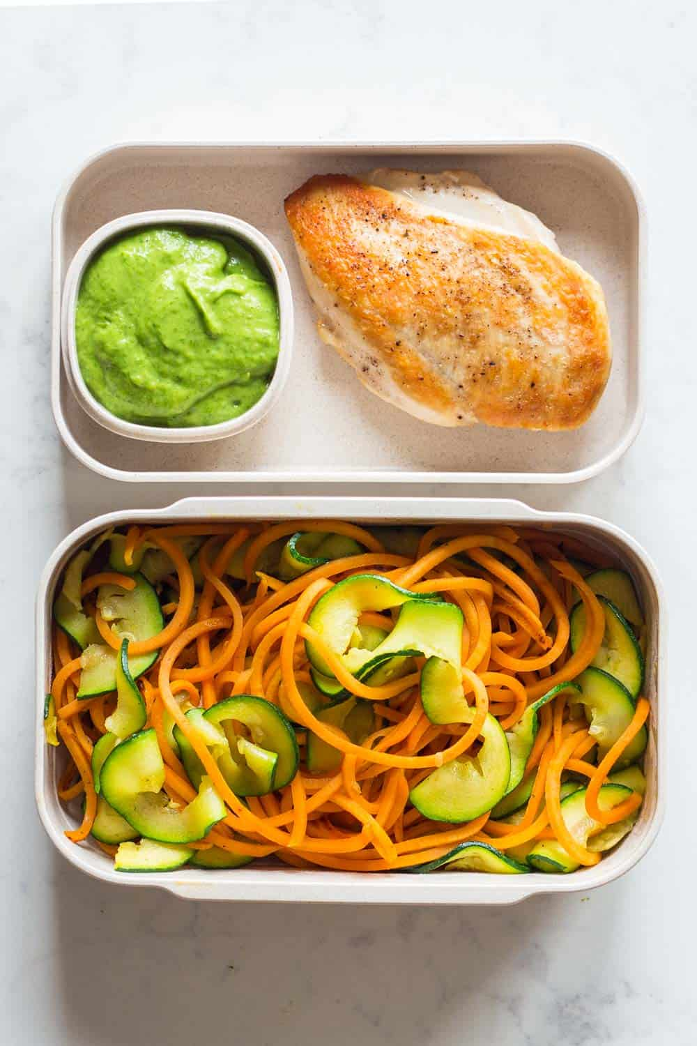 Two meal prep containers filled with pan-fried chicken breast, stir-fried spiralized sweet potato and zucchini with an avocado cilantro dressing on the side.