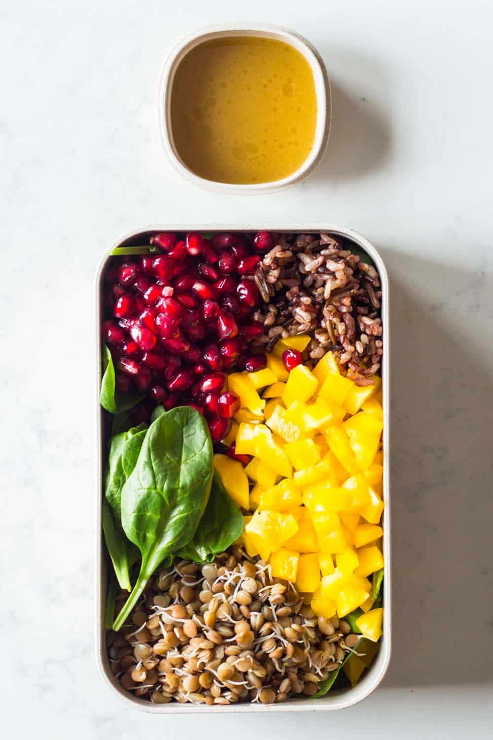 Meal prep container filled with baby spinach, cooked sprouted lentils, cooked wild rice blend, pomegranate seeds, chopped bell pepper and a homemade honey-mustard salad dressing on the side.