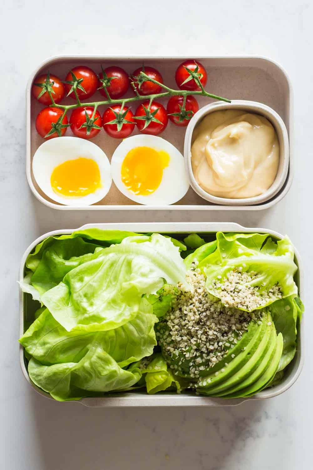 A healthy keto dinner for a complete keto diet plan- butter lettuce, avocado, hemp seed salad with mayonnaise, a soft boiled egg and cherry tomatoes.