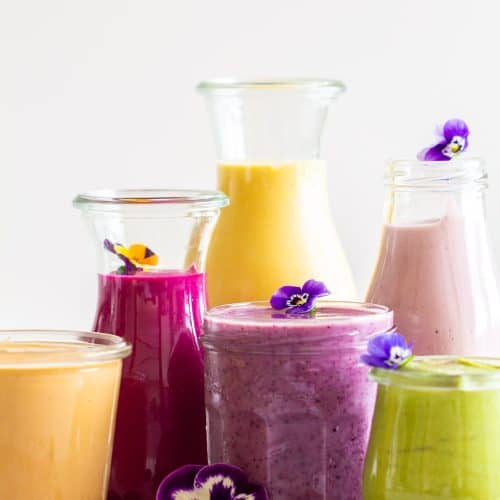 6 healthy breakfast smoothies of different colors in different sized glass jars