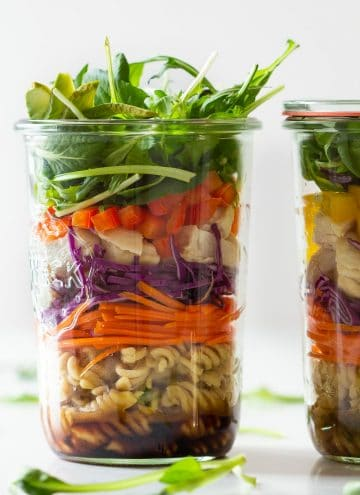 Chicken Pasta Salad in a Jar fille din layers of dressing, pasta, carrot, cabbage, bell pepper, lettuce.