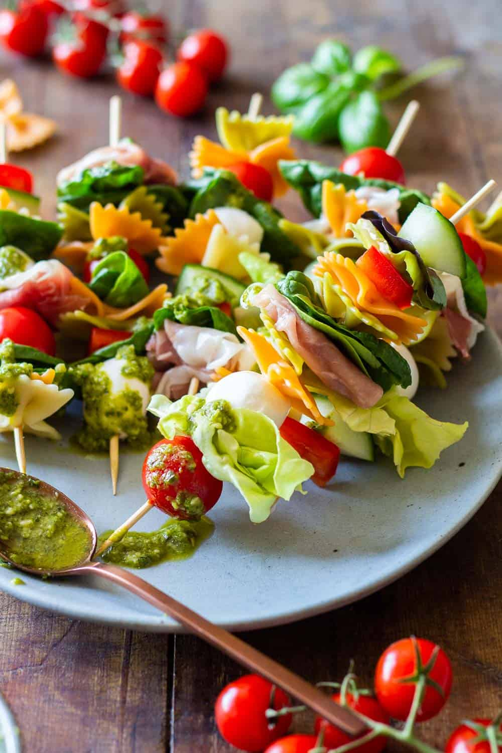 Antipasto Appetizer Skewers arranged on a plate and green pesto on a spoon