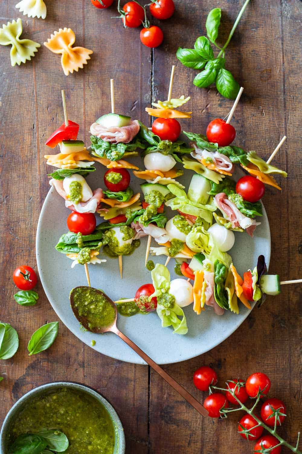 Antipasto Skewers drizzeled with green pesto on a plate